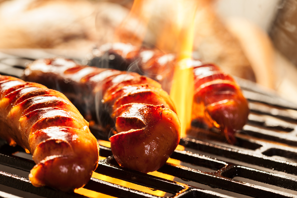 Grilling sausages on barbecue grill. Selective focus